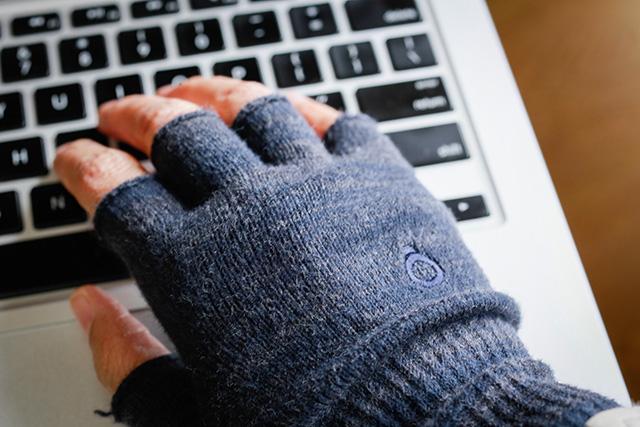 写真:グレーのハンドウォーマーをした手で MacBook Pro を操作する